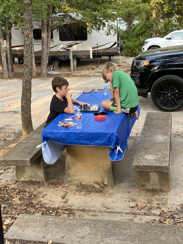 Boys camping and playing chess